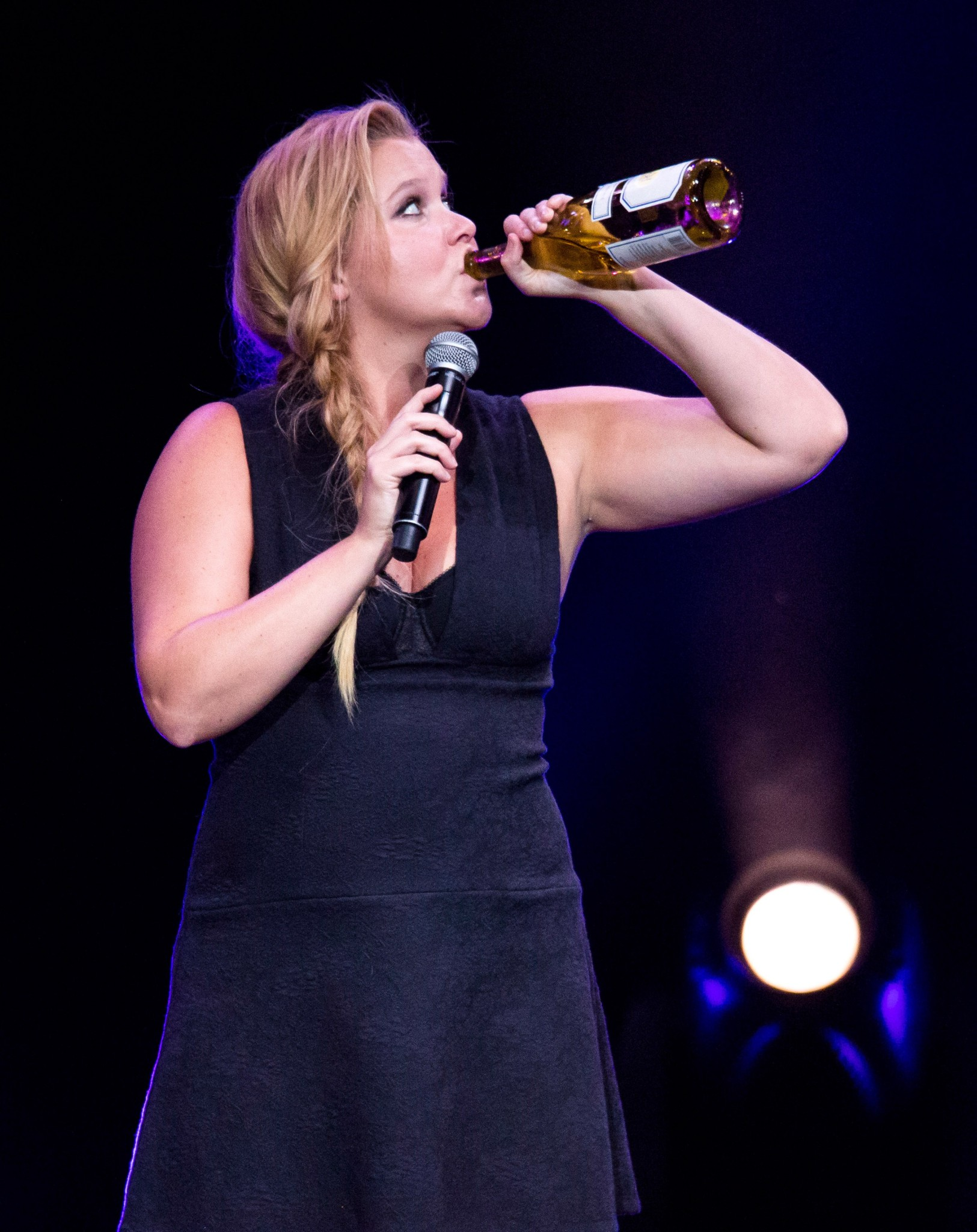 Amy Schumer swigs wine on stage