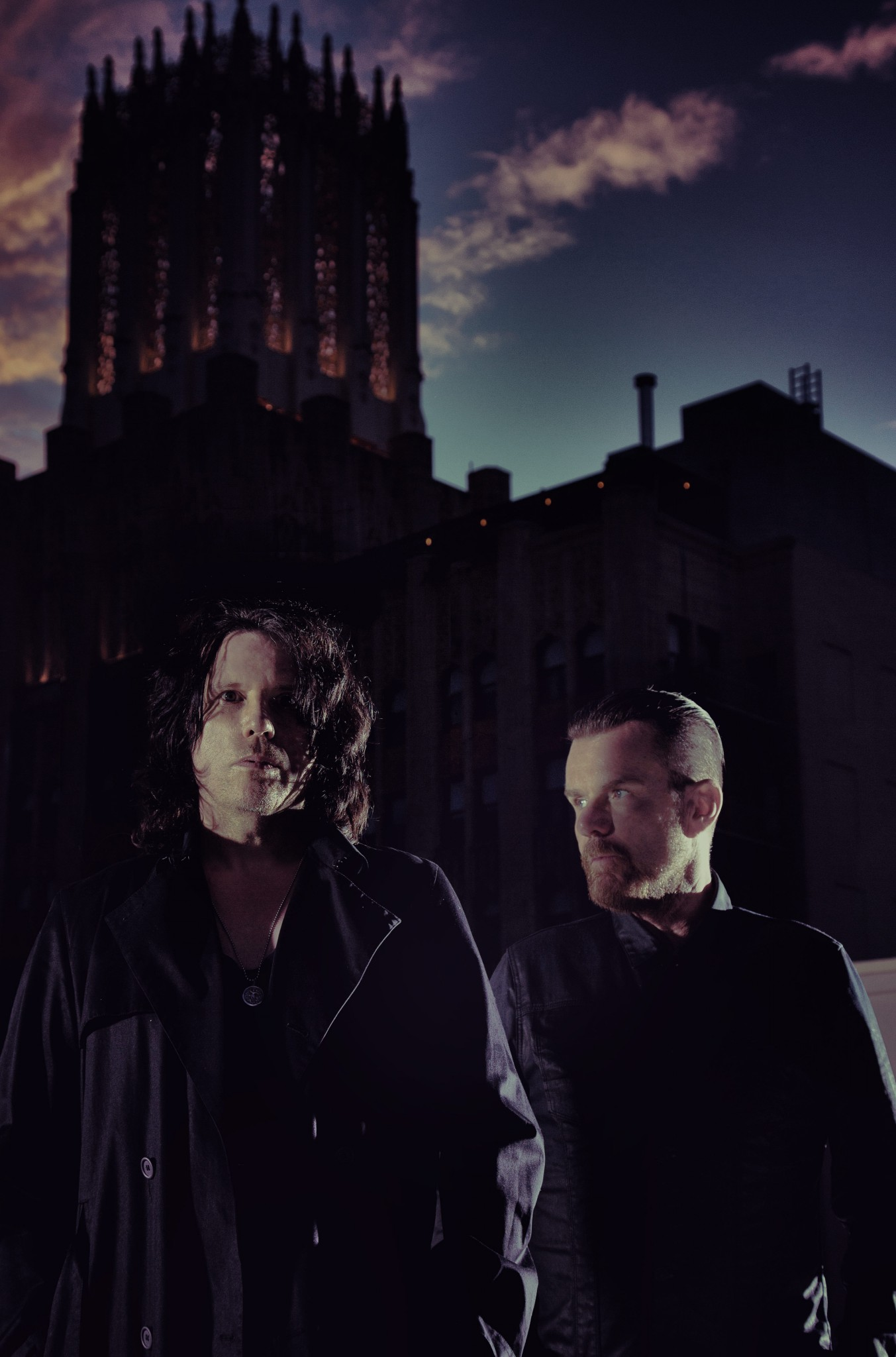 Billy Duffy and Ian Astbury of The Cult stood in front of a dark church – Loaded