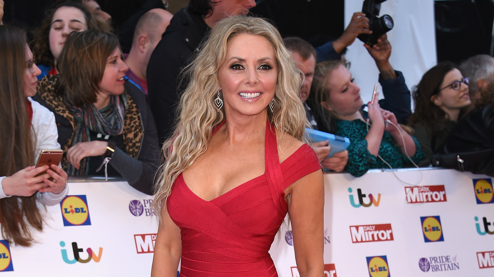 Carol Vorderman poses in a red dress.