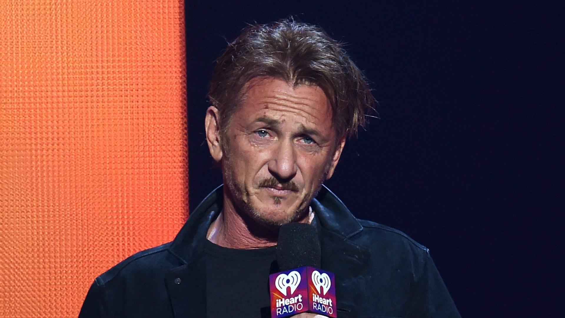 Sean Penn holding a glass and a microphone.