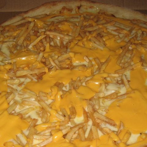 A cheesy pizza with chips.