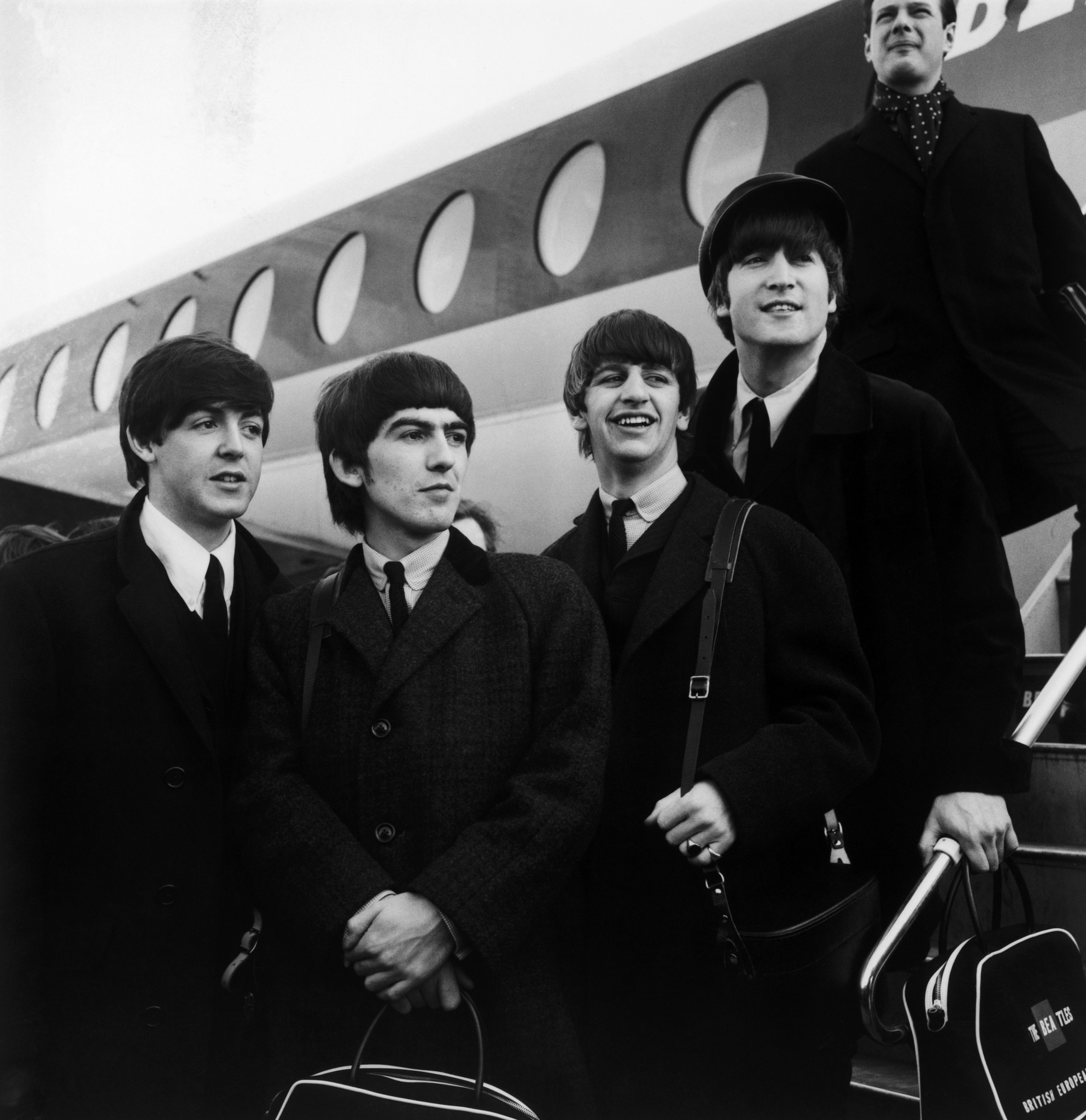 The Beatles board a plane at the height of Beatlemania