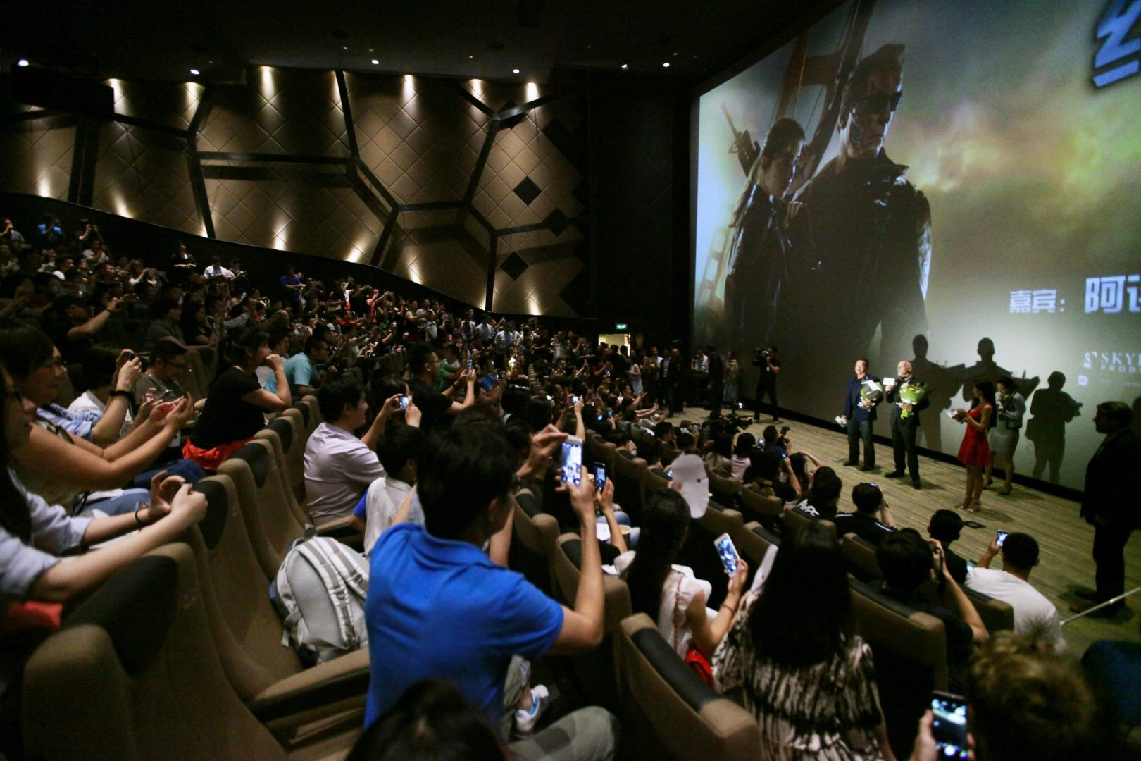 Audiences take picture of Arnold Schwarzenegger and director Alan Taylor at first screening of Terminator Genisys in China.