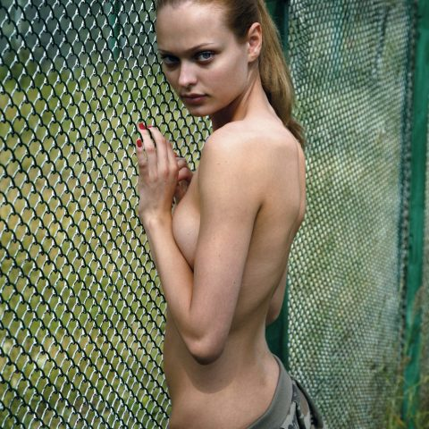 Naked Fashion Girls model poses by a fence