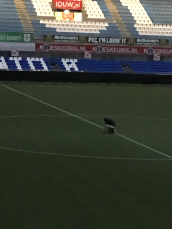 A fan going for a poo on a football pitch.