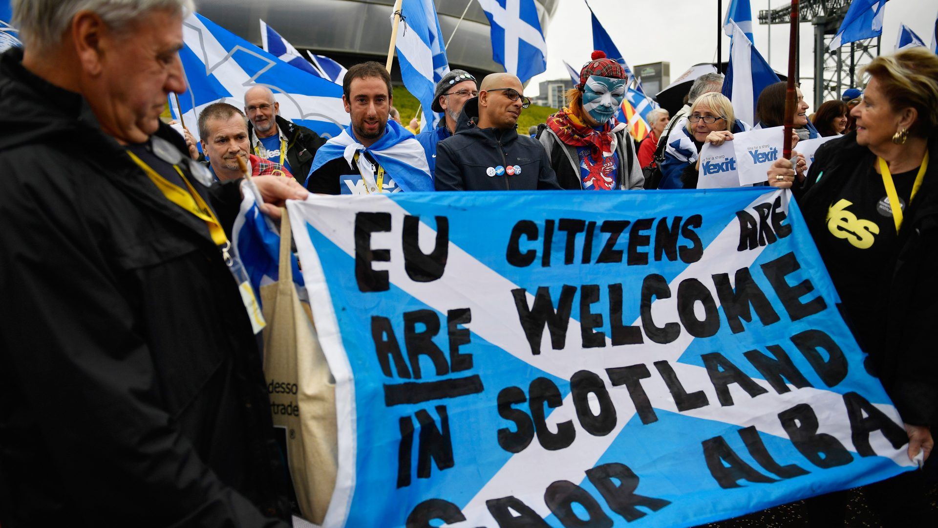 Independence supporters hold up a banner stating that EU citizens are welcome in Scotland as they take part in a rally outside the Scottish National Party conference on October 15, 2016 in Glasgow, Scotland. Nicola Sturgeon is set to end her party's conference with a speech about a 'new political era' in the UK, stating that Scotland is 'open for business' in the post-Brexit era while also speaking about domestic policy priorities.
